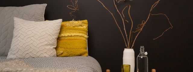 Yellow pillow on neutral wall